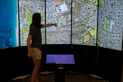 MAT Student infront of a large screen displaying google earth maps