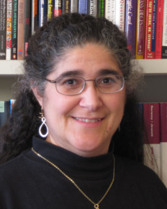 Alice Churukian stands in front of a bookcase. She is a white woman with curly black hair, wearing glasses and a turtleneck sweater.