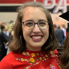 Portrait of Courtney Medina. Courtney is a white woman with brown hair wearing black glasses and a red shirt with flowers on it.