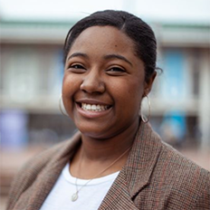 Portrait of Darian Abernathy. Darian is a black woman with straight black hair tied back. She is wearing a white shirt, brown blazer and silver necklace and is smiling at the camera.