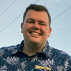 Portrait of Justis Mitchell. Justis is a white man with short brown hair, he is wearing a blue Hawaiian shirt and smiling at the camera.