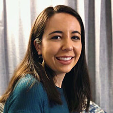 Portrait of Sydney Gutierrez. Sydney is a latina woman with straight brown hair. She is wearing a green shirt and smiling at the camera, sitting in front of a gray curtain.